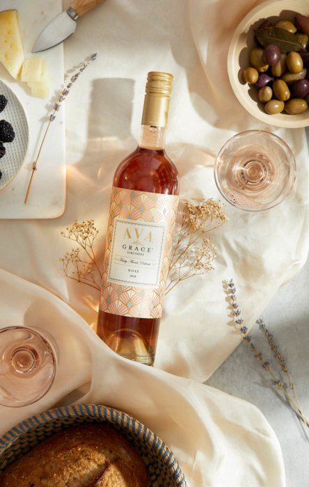 A bottle of rose wine surrounded by cheese