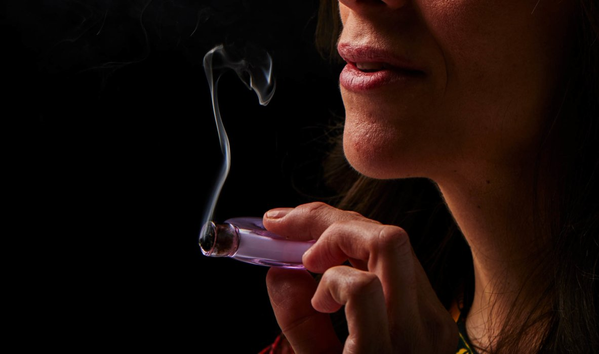 UP close of woman holding a small purple pipe smoking cannabis photography