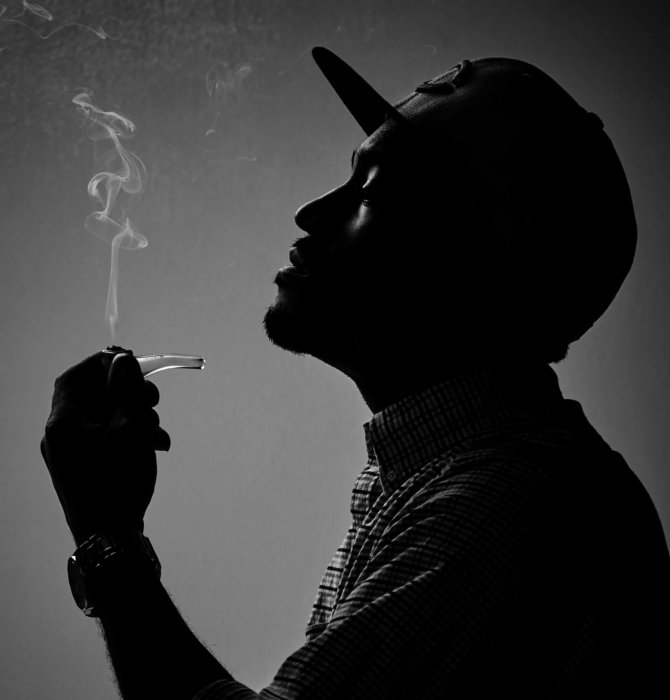 black and white photograph of man with hat looking at smoking pipe cannabis photography