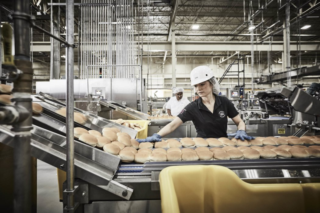 A line worker inspecting buns