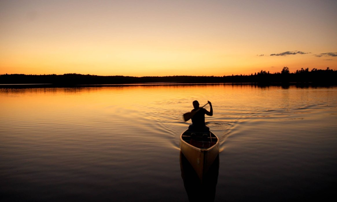A man canoeing on a lake at sunset