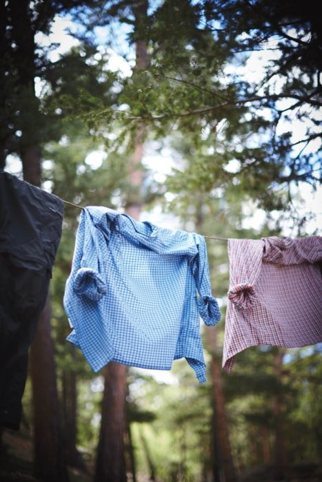 Clothes drying on a line at a campsite in the woods