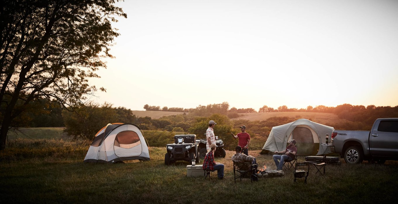 A group of hunters enjoying sunset at their campsite