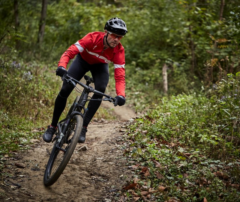 A cyclist riding and leaning on his bike off-road in a forest