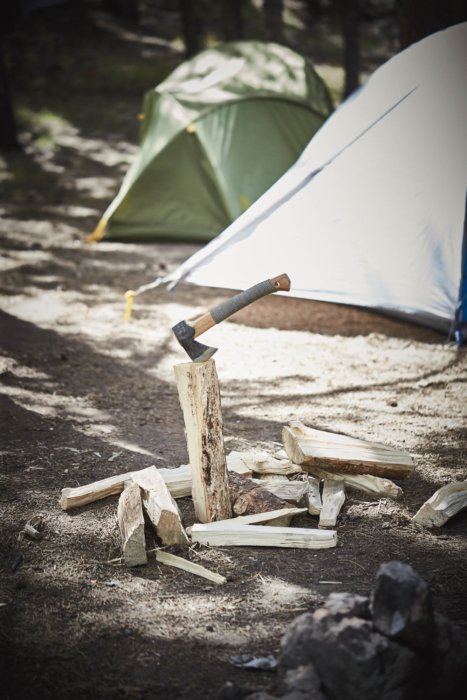 A hatchet at a campsite in a log. Splitting wood.