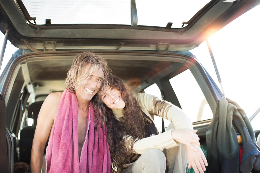 A middle aged couple smiling sitting in the back of their car by a beach