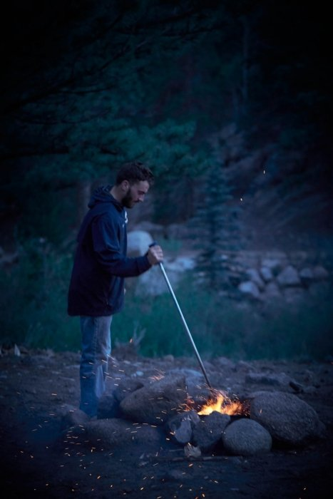 A camper at a campsite stoking a fire