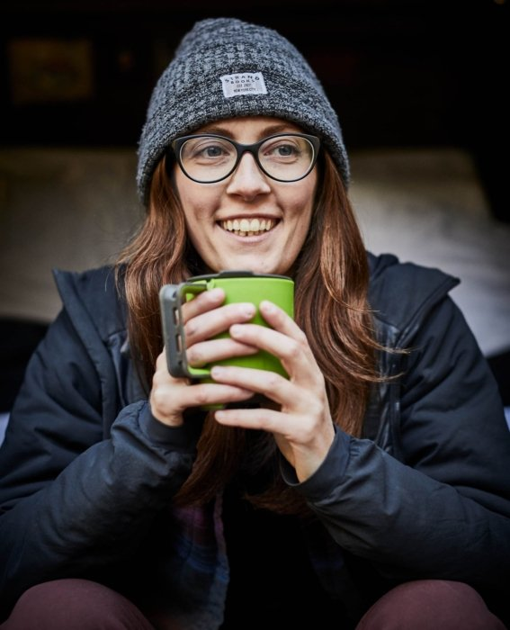 A woman enjoying a cup of coffee at a campsite