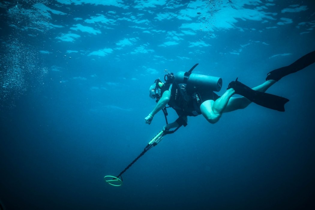A diver with a metal detector in a dark blue ocean