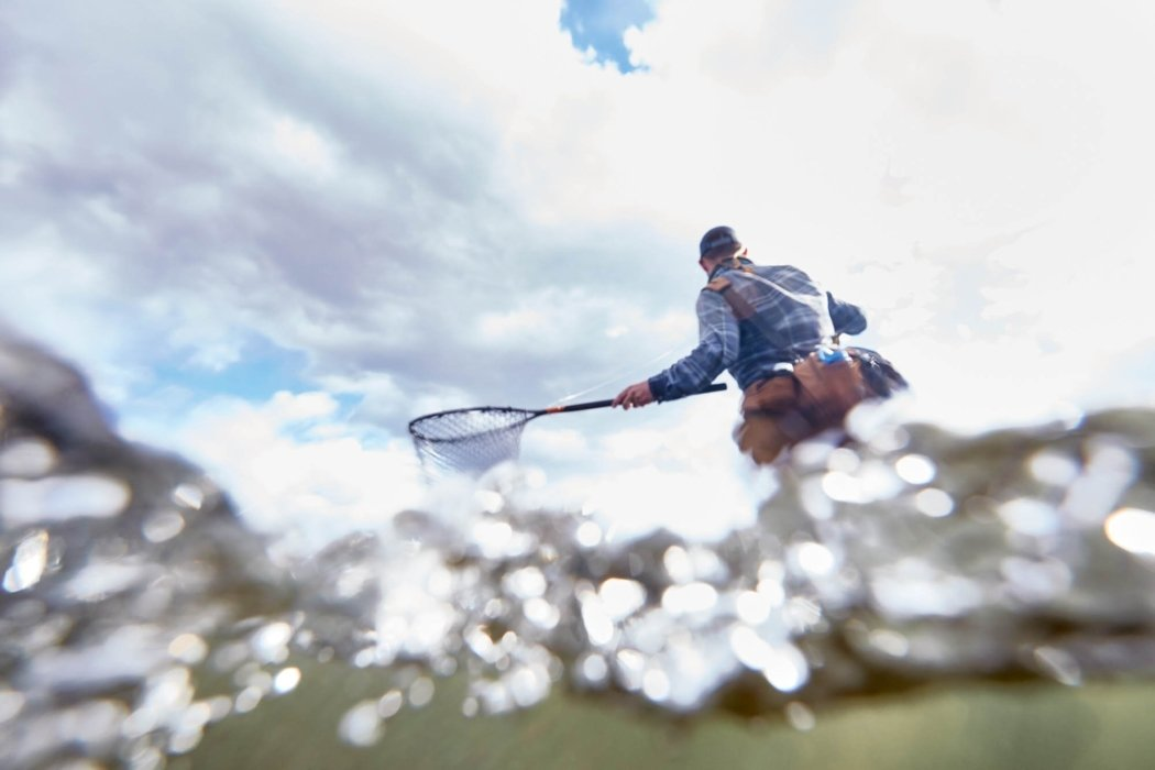 A split shot of a fisherman wading thorough water with a fishing net