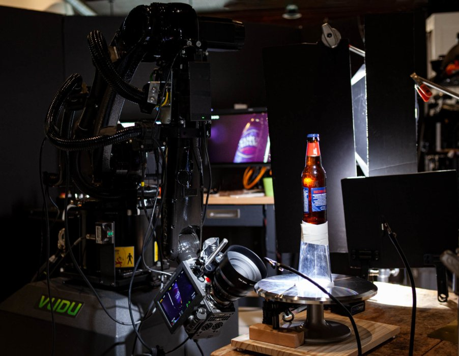 A Sam Adams beer rotating on a turntable with a red camera and VUDU Robotic Sisu System