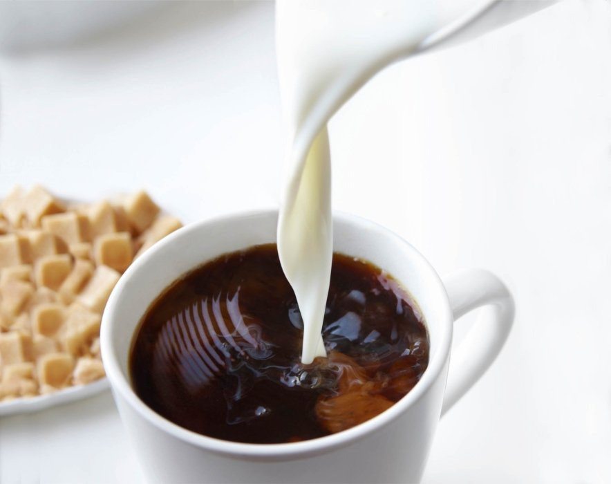 Cream pouring into coffee