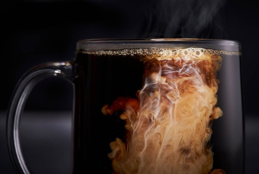Cream swirling into a hot cup of coffee in glass