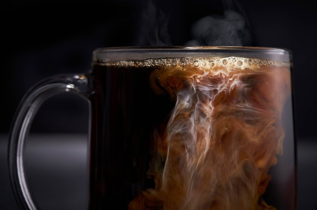 Cream swirling into a hot cup of coffee in glass alternative