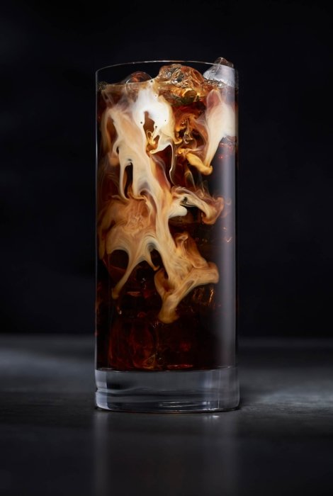 Cream mixing into a glass of iced coffee
