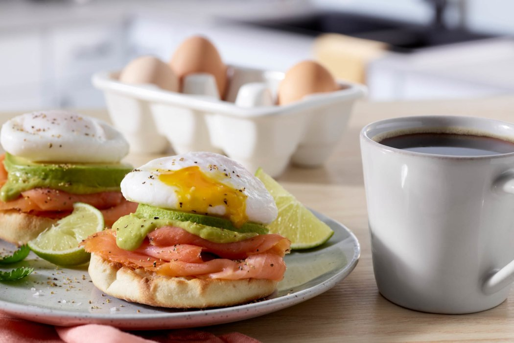 Coffee and a perfectly stacked english muffin with smoked salmon avocado and eggs
