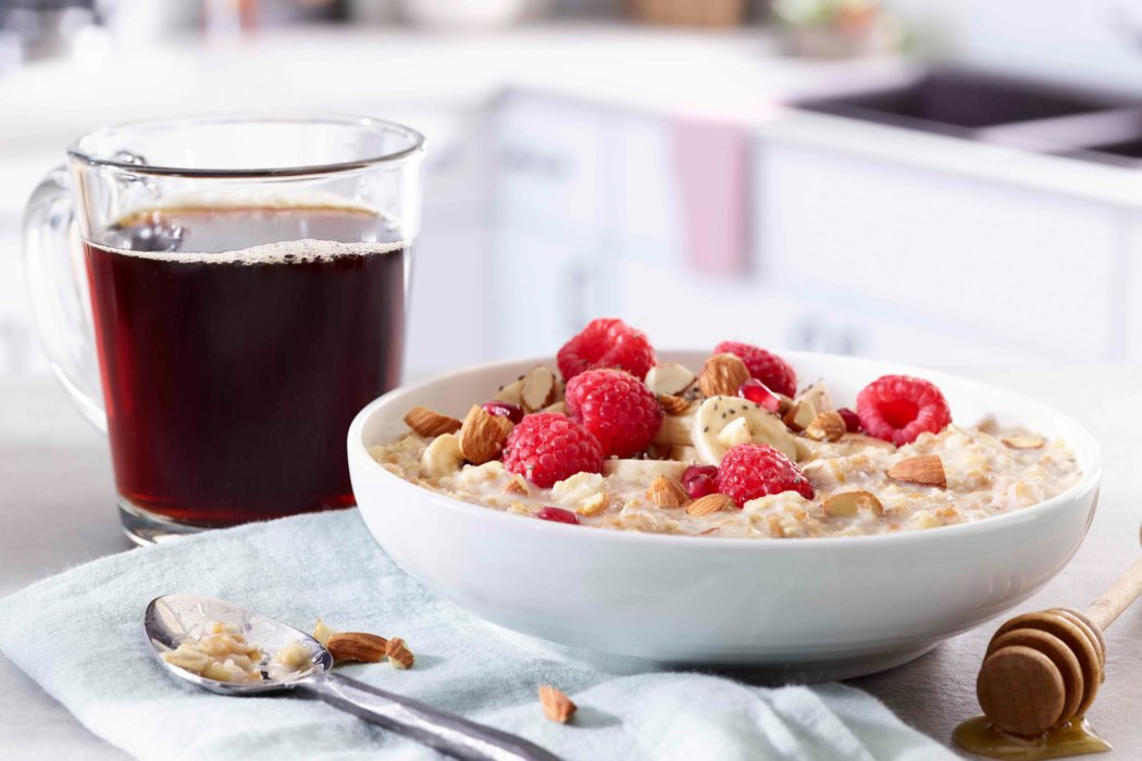 A hot cup of coffee in a glass cup with raspberry oatmeal and honey