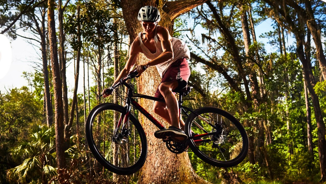 A cyclist doing a bike jump in a forest