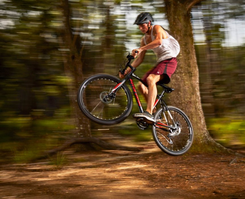 A cyclist doing a bike jump in a forest in motion