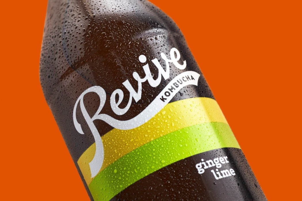 Revive Kombucha ginger lime bottle on an orange background