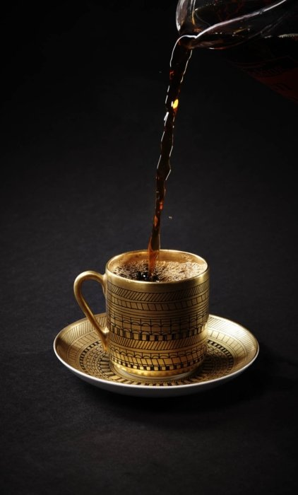 Coffee pouring into an ornate gold coffee cup
