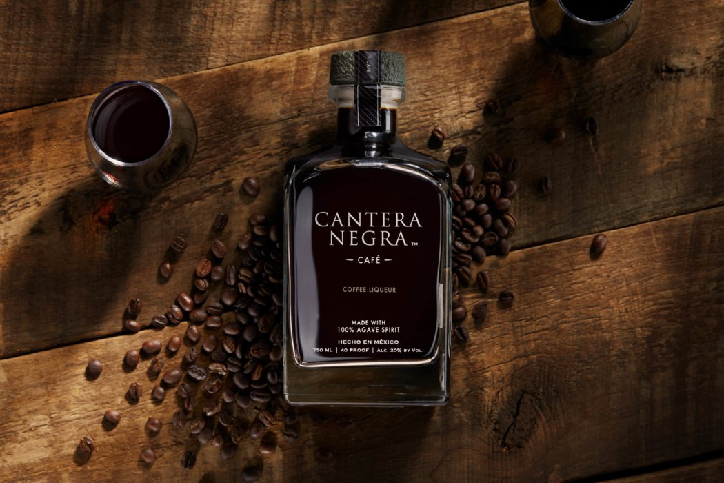 A bottle of cantera negra cafe with coffee beans on a wooden table