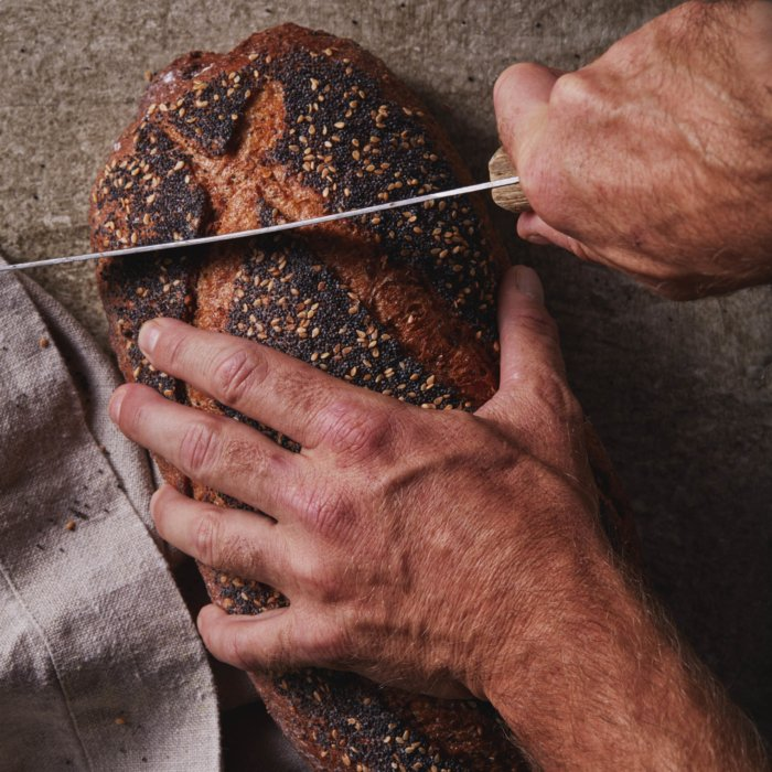 man hands holding fresh baked bread and putting a knife through it