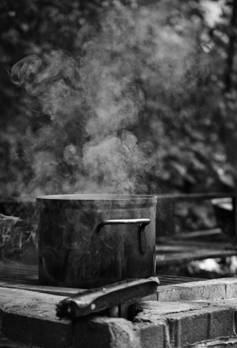 cooking outside with a big pot with steam coming out black and white