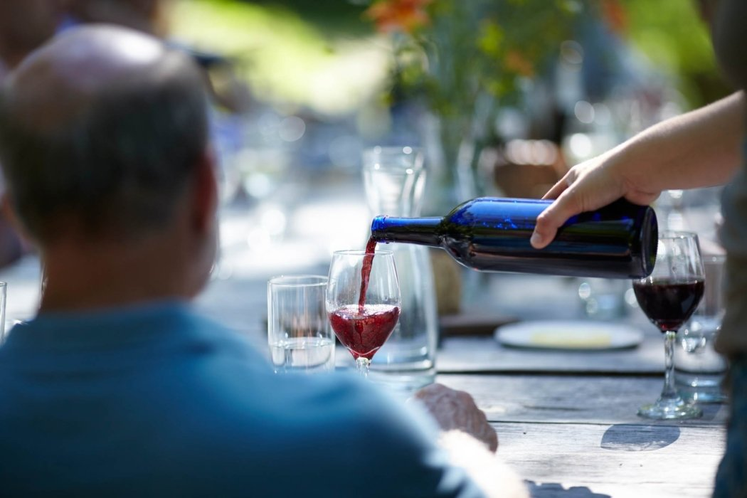 waiter pouring red wine at a food serve restaurant outside