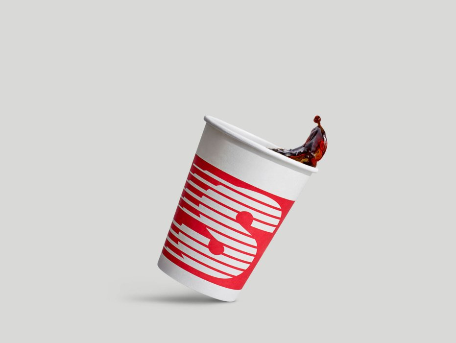 A coffee cup in motion with coffee coming out of the cup