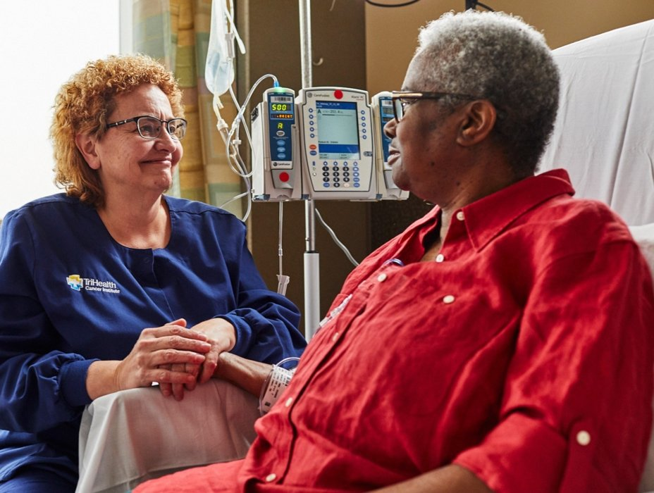 trihealth nurse check in with an older woman who is getting treatments in healthcare