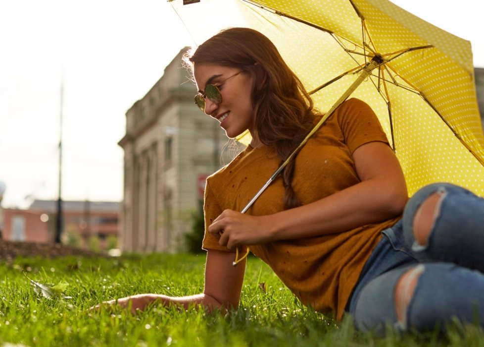 young woman laying on the grass on a sunny day holding up a yellow umbrella