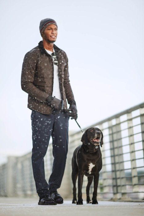 Young man walking his dog outside wearing warm clothes