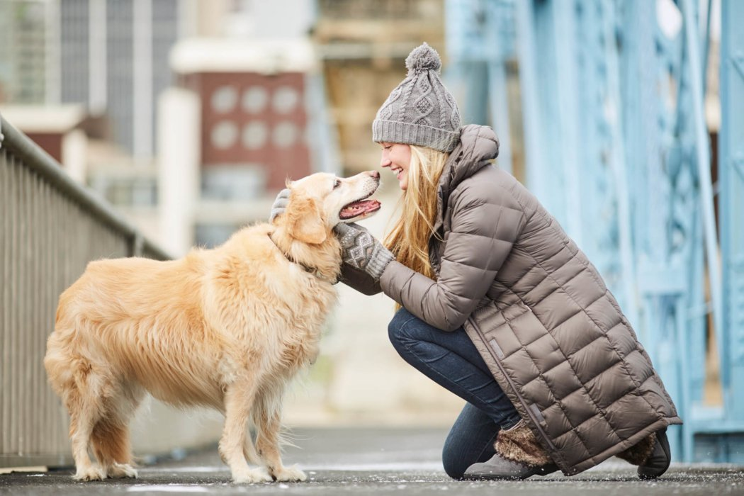 blonde hair woman with brown long coat kneeling down petting a happy dog