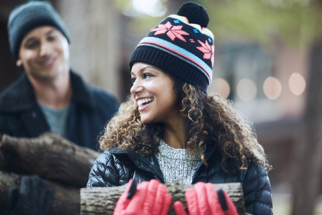 Two people outside with warm clothes and hats carrying piles of logs outside