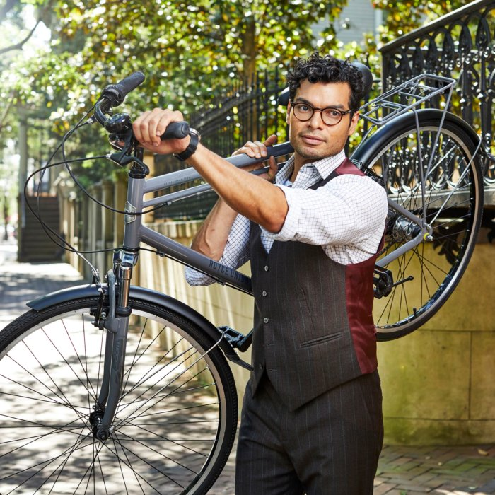 Male that has glasses with a suit holding up a royce union bike outside