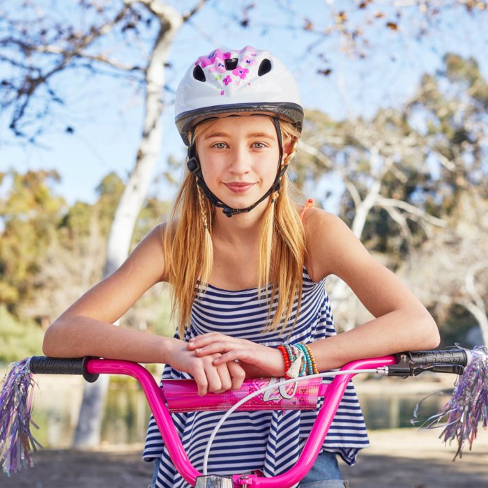 blonde hiar little girl on her pink bike wearing a flower helmet