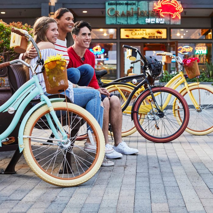 group of three sitting outside with their colorful bikes