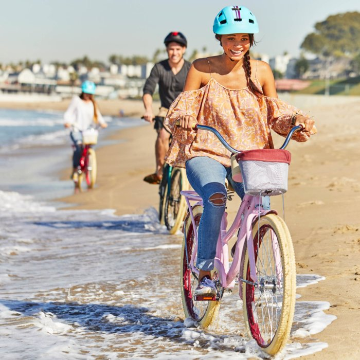 group of three riding their bike on the beach outside wearing helmet