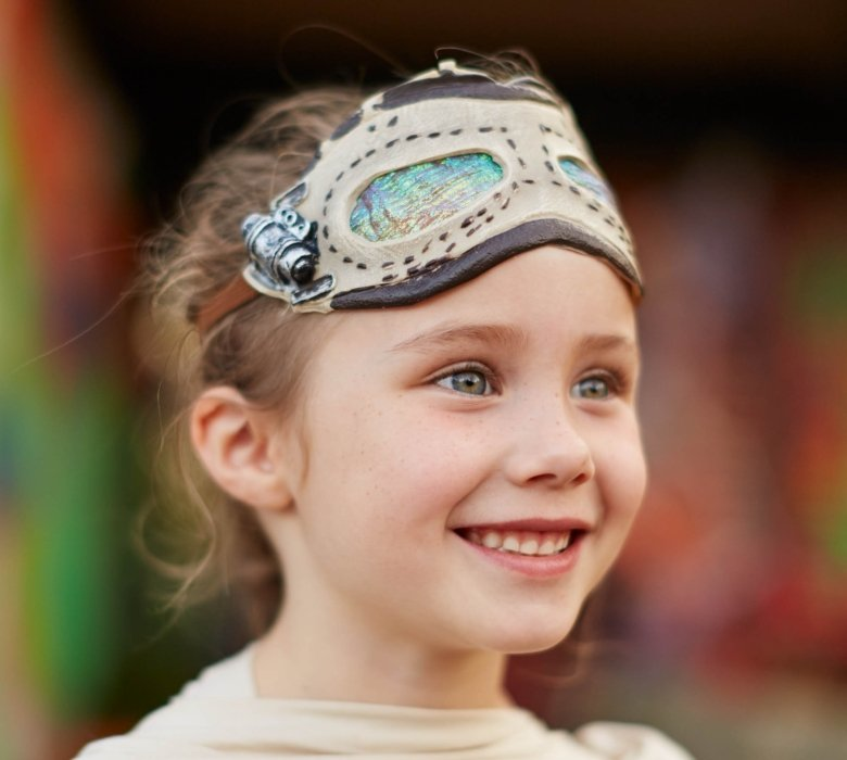 blond hair blue eyes girl smiling with a mask on her head