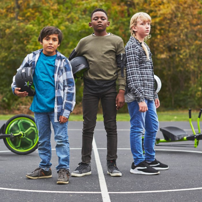 group of three kids on a basketball court holding their helmets bikes in the background