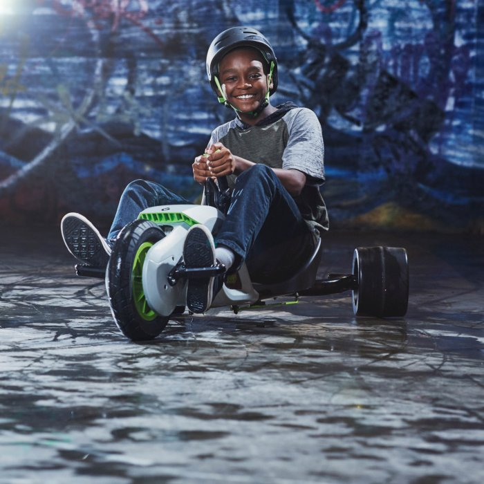 African American boy sitting on a bike wearing a black helmets with green straps sport
