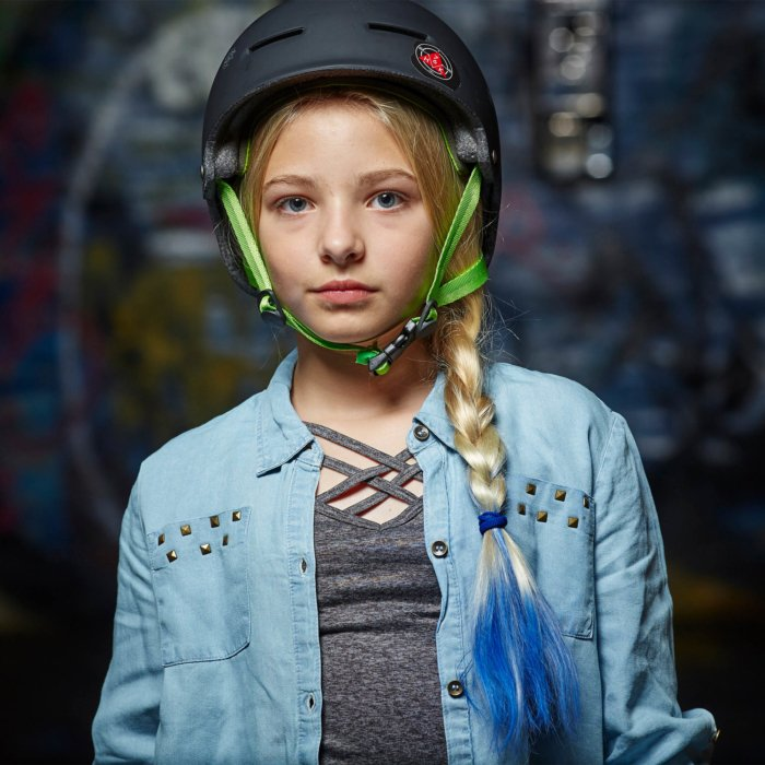 blond hair girl with blue hair on the bottom with a black helmet and green straps sport