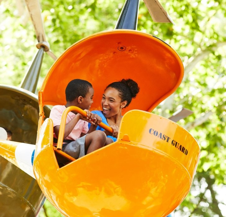 two people smiling and looking at each other while on a ride at a amusement park