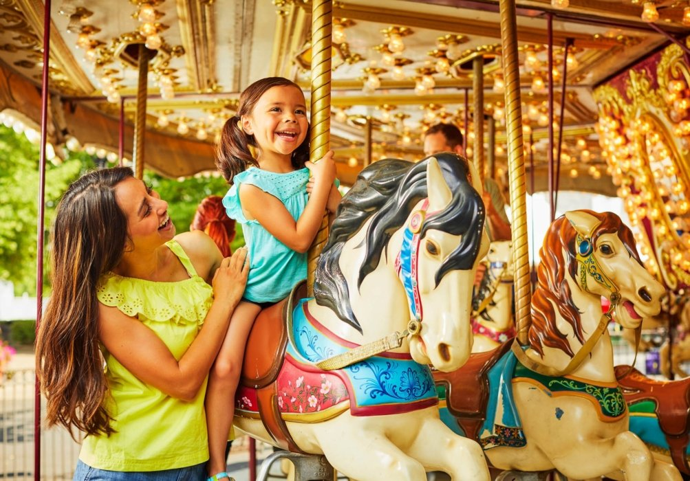 young woman in yellow top holding a little girl with blue top inside of a Carousel Merry Go Round Park