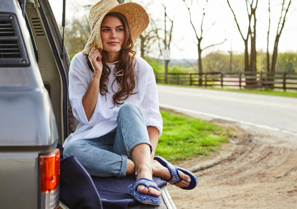 young woman pulling her brown hat down sitting on the car trunk outside wearing blue flip flips