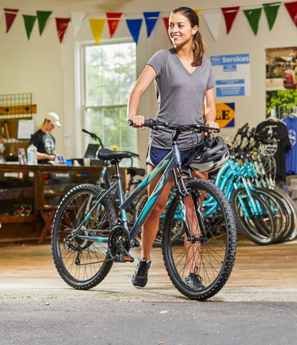 inside bike store brown hiar woman with blue short standing with a blue mountain bike sport