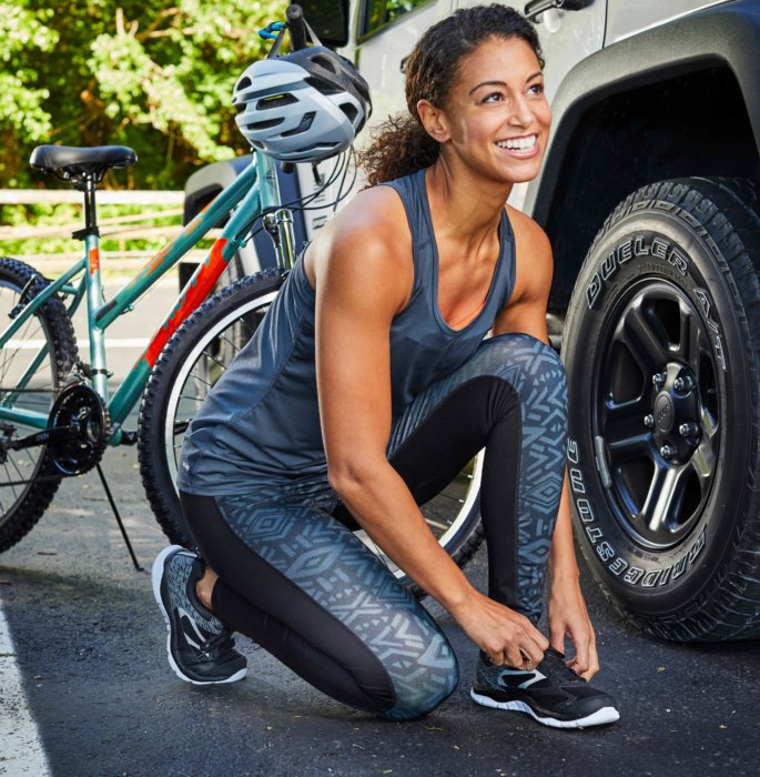 brown hair woman in workout clothes kneeling fixing her shoes next to her bike