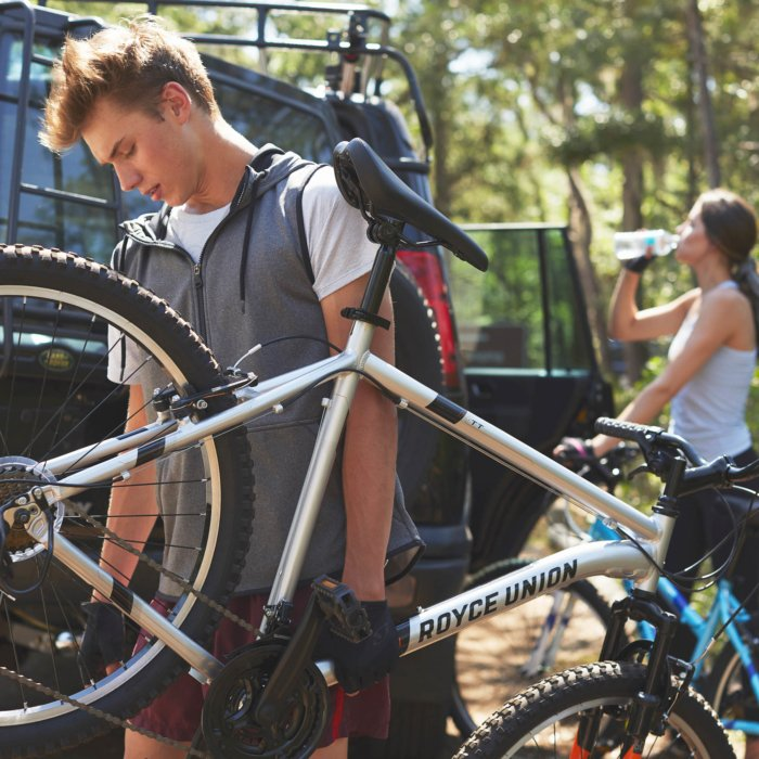 young man holding a silver royce union bike with a girl in the background drinking water sport