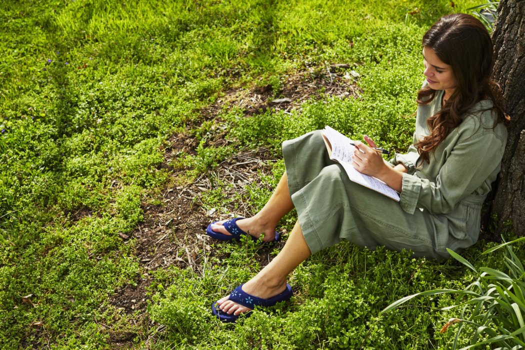 A woman writing in note book wearing acorn sandal - apparel lifestyle photography